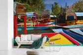 Fotobehang vinyl - Kleurrijke boten bij elkaar in de rivier in Xochimilco in Mexico breedte 420 cm x hoogte 280 cm - Foto print op behang (in 7 formaten beschikbaar)