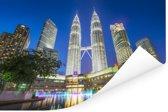 De Petronas Towers verlicht in de avond Poster 90x60 cm - Foto print op Poster (wanddecoratie woonkamer / slaapkamer)