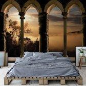 Fotobehang Mountain Sunrise Stone Archway View | VEXXXL - 416cm x 254cm | 130gr/m2 Vlies
