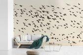 Fotobehang vinyl - Veel grauwe ganzen vliegen door de lucht met een gele hemel breedte 330 cm x hoogte 220 cm - Foto print op behang (in 7 formaten beschikbaar)