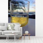 Fotobehang vinyl - Gin en tonic op een tropisch strand breedte 210 cm x hoogte 280 cm - Foto print op behang (in 7 formaten beschikbaar)