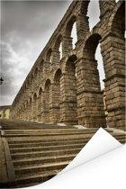 Het Romeinse aquaduct van Segovia in Spanje met een donkere hemel Poster 40x60 cm - Foto print op Poster (wanddecoratie woonkamer / slaapkamer)