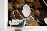 Fotobehang vinyl - Exotische halve kokosnoten op elkaar gestapeld breedte 420 cm x hoogte 280 cm - Foto print op behang (in 7 formaten beschikbaar)