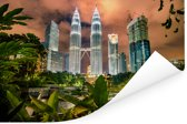De Petronas Towers tussen de bladeren Poster 90x60 cm - Foto print op Poster (wanddecoratie woonkamer / slaapkamer)