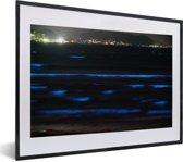 Foto in lijst - Bioluminescent Baai met een stad in Japan fotolijst zwart met witte passe-partout klein 40x30 cm - Poster in lijst (Wanddecoratie woonkamer / slaapkamer)