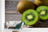 Fotobehang vinyl - Kleurrijke kiwi op een houten tafel breedte 375 cm x hoogte 240 cm - Foto print op behang (in 7 formaten beschikbaar)
