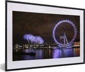 Foto in lijst - Paars vuurwerk en een paarse London Eye in de avond in Londen fotolijst zwart met witte passe-partout 60x40 cm - Poster in lijst (Wanddecoratie woonkamer / slaapkamer)