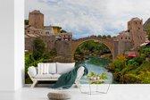 Fotobehang vinyl - Mooie kleurrijke foto van de Stari Most brug en de omgeving breedte 390 cm x hoogte 260 cm - Foto print op behang (in 7 formaten beschikbaar)