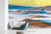 Fotobehang vinyl - Het landschap tijdens een mistige dag in Toscane breedte 600 cm x hoogte 400 cm - Foto print op behang (in 7 formaten beschikbaar)