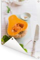 Oranje muskaatpompoen liggend op een tafel Tuinposter 60x90 cm - Tuindoek / Buitencanvas / Schilderijen voor buiten (tuin decoratie)
