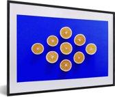 Foto in lijst - Foto van halve sinaasappels op een donkerblauwe achtergrond fotolijst zwart met witte passe-partout 60x40 cm - Poster in lijst (Wanddecoratie woonkamer / slaapkamer)