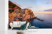 Fotobehang vinyl - Een oranje gekleurd Cinque Terre door de laagstaande zon in Italië breedte 600 cm x hoogte 400 cm - Foto print op behang (in 7 formaten beschikbaar)