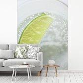 Fotobehang vinyl - Glas gin tonic met een schijfje limoen breedte 255 cm x hoogte 350 cm - Foto print op behang (in 7 formaten beschikbaar)