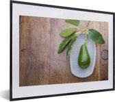 Foto in lijst - Verse avocado op een plaat fotolijst zwart met witte passe-partout klein 40x30 cm - Poster in lijst (Wanddecoratie woonkamer / slaapkamer)