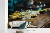 Fotobehang vinyl - Een gin tonic glas op een houten bar breedte 525 cm x hoogte 350 cm - Foto print op behang (in 7 formaten beschikbaar)