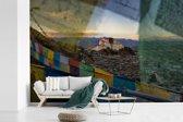 Fotobehang vinyl - Het Potalapaleis tussen gekleurde vlaggen in Lhasa breedte 420 cm x hoogte 280 cm - Foto print op behang (in 7 formaten beschikbaar)