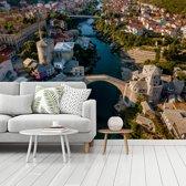 Fotobehang vinyl - De Stari Most brug vanaf boven in Bosnië en Herzegovina breedte 350 cm x hoogte 260 cm - Foto print op behang (in 7 formaten beschikbaar)