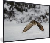 Foto in lijst - Een oehoe vliegt laag over de sneeuw heen fotolijst zwart 60x40 cm - Poster in lijst (Wanddecoratie woonkamer / slaapkamer)