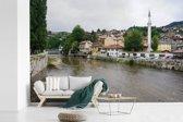 Fotobehang vinyl - Miljacka rivier in Sarajevo in Bosnië en Herzegovina breedte 390 cm x hoogte 260 cm - Foto print op behang (in 7 formaten beschikbaar)