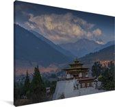 Uitzicht op de wolken met het Punakha Dzong klooster op de voorgrond Canvas 30x20 cm - klein - Foto print op Canvas schilderij (Wanddecoratie woonkamer / slaapkamer)