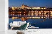 Fotobehang vinyl - Reflectie van schitterend gebouwen in de Moldau tijdens het blauwe uur in Tsjechië breedte 330 cm x hoogte 220 cm - Foto print op behang (in 7 formaten beschikbaar)