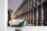 Fotobehang vinyl - Beeld langs het Romeinse aquaduct van Segovia breedte 600 cm x hoogte 400 cm - Foto print op behang (in 7 formaten beschikbaar)
