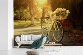 Fotobehang vinyl - Bloemen in de fietsmand van de fiets breedte 600 cm x hoogte 400 cm - Foto print op behang (in 7 formaten beschikbaar)