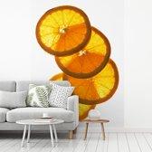 Fotobehang vinyl - Sinaasappel schijven op elkaar gestapeld met doorschijnend licht breedte 190 cm x hoogte 280 cm - Foto print op behang (in 7 formaten beschikbaar)
