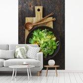 Fotobehang vinyl - Rucola op een donker bord met een houten snijplank breedte 215 cm x hoogte 320 cm - Foto print op behang (in 7 formaten beschikbaar)