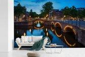 Fotobehang vinyl - Verlichte Prinsengracht in de avond breedte 450 cm x hoogte 300 cm - Foto print op behang (in 7 formaten beschikbaar)