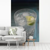 Fotobehang vinyl - Een Gin tonic op een blauwe tafel breedte 175 cm x hoogte 260 cm - Foto print op behang (in 7 formaten beschikbaar)