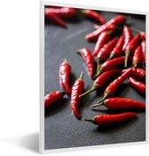 Foto in lijst - Rode cayennepepers op grijze ondergrond fotolijst wit 30x40 cm - Poster in lijst (Wanddecoratie woonkamer / slaapkamer)