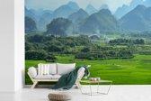 Fotobehang vinyl - De Rijstterrassen van Lóngjĭ met op de achtergrond mooie bergen breedte 360 cm x hoogte 240 cm - Foto print op behang (in 7 formaten beschikbaar)