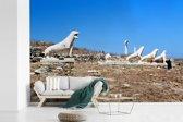 Fotobehang vinyl - Uitzicht op De Leeuwen van Delos breedte 450 cm x hoogte 300 cm - Foto print op behang (in 7 formaten beschikbaar)