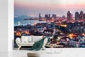 Fotobehang vinyl - Uitzicht over Qingdao in de avond breedte 540 cm x hoogte 360 cm - Foto print op behang (in 7 formaten beschikbaar)