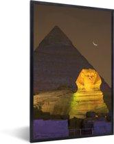 Foto in lijst - Kleine maan bij de Sfinx van Gizeh in de nacht in Egypte fotolijst zwart 40x60 cm - Poster in lijst (Wanddecoratie woonkamer / slaapkamer)
