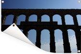 Het donkere Romeinse aquaduct van het Spaanse Segovia Tuinposter 60x40 cm - klein - Tuindoek / Buitencanvas / Schilderijen voor buiten (tuin decoratie)