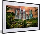 Foto in lijst - De Petronas Towers tussen de bladeren fotolijst zwart met witte passe-partout 60x40 cm - Poster in lijst (Wanddecoratie woonkamer / slaapkamer)