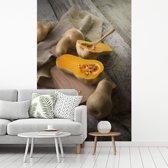 Fotobehang vinyl - Muskaatpompoen op houten snijplank breedte 215 cm x hoogte 320 cm - Foto print op behang (in 7 formaten beschikbaar)