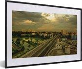 Foto in lijst - Gele tinten in de lucht boven Dhaka fotolijst zwart met witte passe-partout 60x40 cm - Poster in lijst (Wanddecoratie woonkamer / slaapkamer)