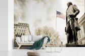 Fotobehang vinyl - Zwart-wit foto van standbeeld van George Washington met de Amerikaanse vlag breedte 450 cm x hoogte 300 cm - Foto print op behang (in 7 formaten beschikbaar)
