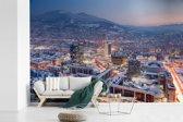 Fotobehang vinyl - Straatbeeld van Sarajevo en berg met sneeuw in Bosnië en Herzegovina breedte 390 cm x hoogte 260 cm - Foto print op behang (in 7 formaten beschikbaar)